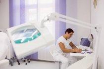 Médecin assis et écrivant sur le presse-papiers au bureau de la clinique — Photo de stock
