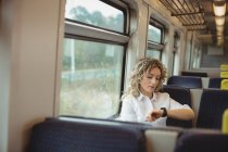 Worried businesswoman checking time while travelling in train — Stock Photo