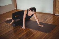 Femme saine faisant de l'exercice avec rouleau de mousse dans un studio de fitness — Photo de stock