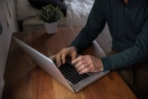 Sección media del hombre que utiliza el ordenador portátil en la sala de estar en casa - foto de stock
