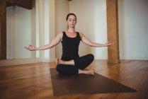 Woman practicing yoga in fitness studio — Stock Photo