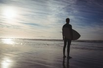 Silhouette of surfer standing with surfboard on beach — Stock Photo