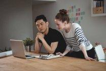 Dirigeants d'entreprise discutant sur ordinateur portable au bureau — Photo de stock