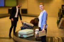 Коммутеры забирают его багаж из зоны выдачи багажа в аэропорту — стоковое фото