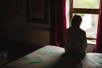 Femme assise sur le lit dans la chambre — Photo de stock