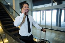 Businessman on escalator talking on mobile phone in airport — Stock Photo