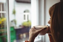 Gros plan de la femme prenant un café à la fenêtre du restaurant — Photo de stock