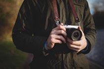 Sezione centrale dell'uomo che tiene la telecamera all'aperto — Foto stock