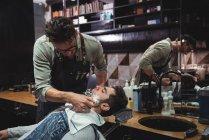 Перукарня, застосовуючи крем клієнт борода в перукарні — стокове фото
