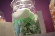Primer plano de los dulces turcos en frasco de vidrio dispuestos en el estante en la tienda - foto de stock