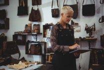 Зрелая ремесленница с помощью цифрового планшета в мастерской — стоковое фото