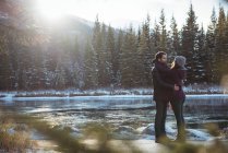 Romantic couple embracing by river in winter — Stock Photo