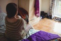 Femme assise sur le lit dans la chambre à coucher à la maison — Photo de stock