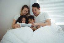 Семья с помощью цифрового планшета в спальне на дому — стоковое фото