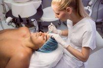 Médecin injectant du botox à un patient de sexe masculin à la clinique — Photo de stock