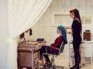 Kosmetikerin stylt Kunden Haare in Dreadlocks — Stockfoto