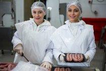 Porträt von Fleischerinnen beim Würstchenpacken in Fleischfabrik — Stockfoto