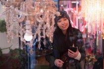 Mulher olhando para lustres na loja vintage — Fotografia de Stock