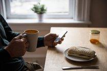 Средняя часть тела мужчины, пользующегося мобильным телефоном за чашкой кофе дома — стоковое фото