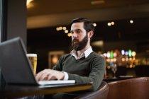 Hombre usando el ordenador portátil en el interior del bar con cerveza en la mesa - foto de stock