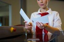 Mitte weibliches Personal mit Bordkarten im Flughafenterminal — Stockfoto