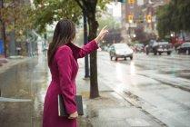 Donna d'affari chiama un taxi dal marciapiede della città — Foto stock
