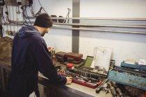 Mechanic checking various tools in repair garage — Stock Photo