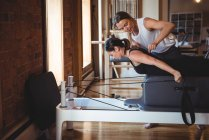 Trainer helping a woman while practicing pilates in fitness studio — Stock Photo