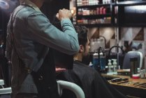 Barber showing man haircut in mirror in barber shop — Stock Photo