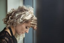 Close-up of upset businesswoman leaning on window in office — Stock Photo