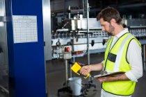 Вид сбоку рабочего-мужчины, использующего механическую обработку на соковом заводе — стоковое фото