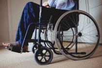 Gros plan d'un aîné assis en fauteuil roulant à la maison — Photo de stock