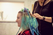Beautician styling clients hair in dreadlocks shop — Stock Photo
