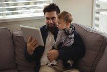Padre con tableta digital mientras sostiene a su bebé en casa - foto de stock