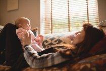 Мать играет с младенческой дочерью на диване в гостиной — стоковое фото