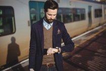 Empresário verificando o tempo em smartwatch na estação ferroviária — Fotografia de Stock