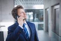 Businessman talking on mobile phone in office — Stock Photo