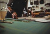 Meados de seção de artesã organizando peça de couro na oficina — Fotografia de Stock