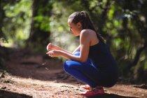 Женщина, сидящая на корточках на лесной дорожке в солнечный день — стоковое фото