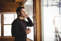 Homem ao telefone na frente da janela com café — Fotografia de Stock
