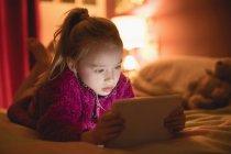 Fille couchée sur l'avant sur le lit et en utilisant une tablette numérique dans la chambre à coucher à la maison — Photo de stock