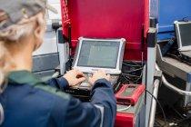Женщина-механик с ноутбуком в ремонтном гараже — стоковое фото