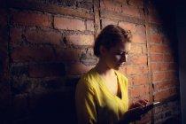Donna in piedi contro muro di mattoni e utilizzando il telefono cellulare — Foto stock