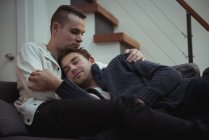 Gay couple embracing on sofa at home — Stock Photo