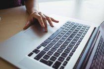 La mano de la mujer de negocios que trabaja en el portátil en la oficina - foto de stock
