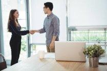 Executivos de negócios apertando a mão uns dos outros no escritório — Fotografia de Stock