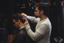 Homme se faire couper les cheveux par coiffeur avec tondeuse dans le salon de coiffure — Photo de stock