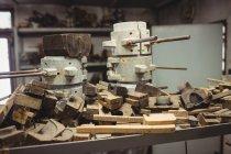 Металлические и деревянные формы для стеклодувки расположены на полке на стеклодувном заводе — стоковое фото