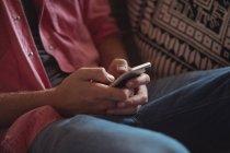 Primo piano di un uomo che tiene il cellulare in salotto — Foto stock