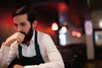 Serveur réfléchi debout près du comptoir du bar au bar — Photo de stock
